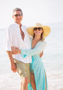 Middle aged couple enjoying walk on the beach happy romantic vacation retirement concept Royalty Free Stock Images