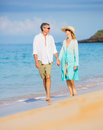 Middle aged couple enjoying walk on the beach happy romantic vacation retirement concept Stock Photo