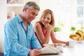 Middle aged couple having breakfast in kitchen together reading newspaper Stock Images