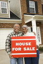 Middle-aged couple holding a for sale sign. Stock Photos