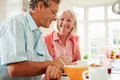 Middle aged couple looking at digital tablet over breakfast home smiling Stock Photos