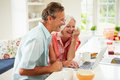 Middle aged couple looking at laptop over breakfast in kitchen laughing Stock Photo