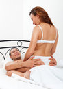 Middle aged couple making love on white sheet in bed at home Stock Photo