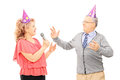 Middle aged couple with party hats dancing and singing on microphone isolated on white background Royalty Free Stock Photography