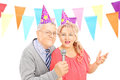 Middle aged couple with party hats singing on microphone isolated white background Royalty Free Stock Photos