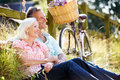 Middle aged couple relaxing on country cycle ride looking into distance smiling Royalty Free Stock Image