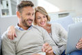 Middle aged couple relaxing in sofa using tablet and Royalty Free Stock Photography