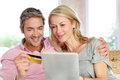 Middle aged couple shopping online with credit card sitting in sofa at home and doing Royalty Free Stock Image