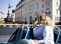 A middle-aged couple sitting on a sightseeing bus, taking photographs Royalty Free Stock Photo