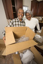 Middle-aged couple unpacking boxes. Stock Photos