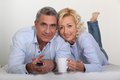 Middle aged couple watching television together Royalty Free Stock Images