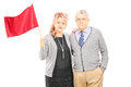 Middle aged couple waving a red flag isolated on white background Stock Photo
