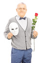 Middle aged gentleman holding rose flower and mask isolated on white background Stock Photography