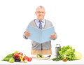 Middle aged gentleman reading a cookbook during a preparation of salad isolated on white background Stock Photos