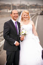 Middle aged groom and bride walking on highway closeup portrait of Stock Image