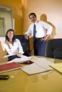 Middle-aged Hispanic businessman and assistant Stock Images
