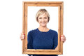 Middle aged lady holding photo frame smiling woman standing behind wooden picture Royalty Free Stock Photography