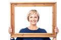 Middle aged lady holding photo frame standing behind wooden picture Stock Photography