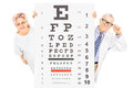 Middle aged male doctor and female patient standing behind eyesi eyesight test isolated on white background Royalty Free Stock Photos