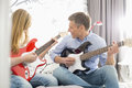 Middle-aged man with daughter playing guitars at home Royalty Free Stock Photo