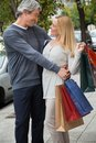Middle aged man embracing woman happy men women on sidewalk while carrying shopping bags Stock Photo