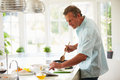 Middle aged man following recipe on digital tablet in kitchen holding wooden spoon Royalty Free Stock Photography