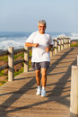 Middle aged man jogging active happy at the beach in the morning Royalty Free Stock Photo