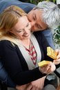 Middle aged man kissing woman affectionate men women as she opens present Royalty Free Stock Image
