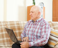 Middle aged man with laptop elderly gray haired at his on sofa at home Stock Photo