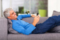 Middle aged man reading message text on mobile phone while lying on couch Royalty Free Stock Photo