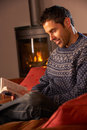Middle Aged Man Relaxing With Book By Cosy Fire Stock Photo