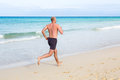 Middle aged man running jogging in summer on a beach Stock Photography