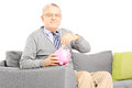 Middle aged man seated on sofa putting money into piggybank Stock Image