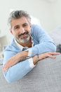 Middle-aged man sitting on sofa and relaxing Royalty Free Stock Photo