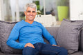 Middle aged man sofa cheerful relaxing on at home Stock Photos