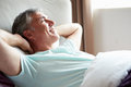 Middle aged man waking up in bed looking away from camera smiling Stock Photography