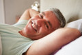 Middle aged man waking up in bed looking to camera smiling Stock Photo