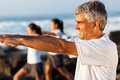 Middle aged man workout side view of healthy with family at the beach Stock Photography