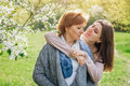 Middle-aged mother and her daughter hugging in blooming garden Royalty Free Stock Photo