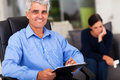 Middle aged psychologist portrait of male in office with patient in background Royalty Free Stock Images