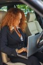 Middle aged redhead businesswoman beautiful in black jacket with laptop behind steering wheel Royalty Free Stock Image