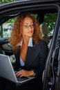 Middle aged redhead businesswoman beautiful in black jacket with laptop behind steering wheel Royalty Free Stock Images