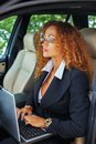 Middle aged redhead businesswoman beautiful in black jacket with laptop behind steering wheel Stock Image