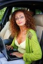 Middle aged redhead woman in car beautiful with laptop behind steering wheel Royalty Free Stock Photos