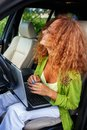 Middle aged redhead woman with laptop beautiful behind steering wheel Royalty Free Stock Photo