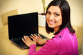 Middle aged smiling woman using laptop and looking on the camera Royalty Free Stock Image