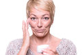 Middle aged woman applying anti aging cream attractive blond to the wrinkles around her eyes in an effort to combat in a Royalty Free Stock Images