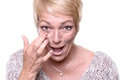 Middle aged woman applying anti aging cream attractive blond to the wrinkles around her eyes in an effort to combat in a Stock Images