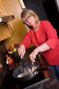 Middle aged woman cooking. Royalty Free Stock Photos