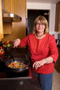 Middle aged woman cooking. Royalty Free Stock Photo